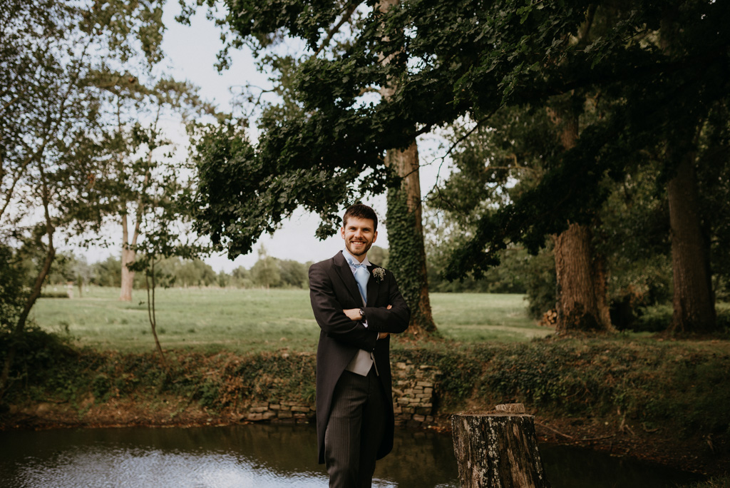marié costum étang arbre pose