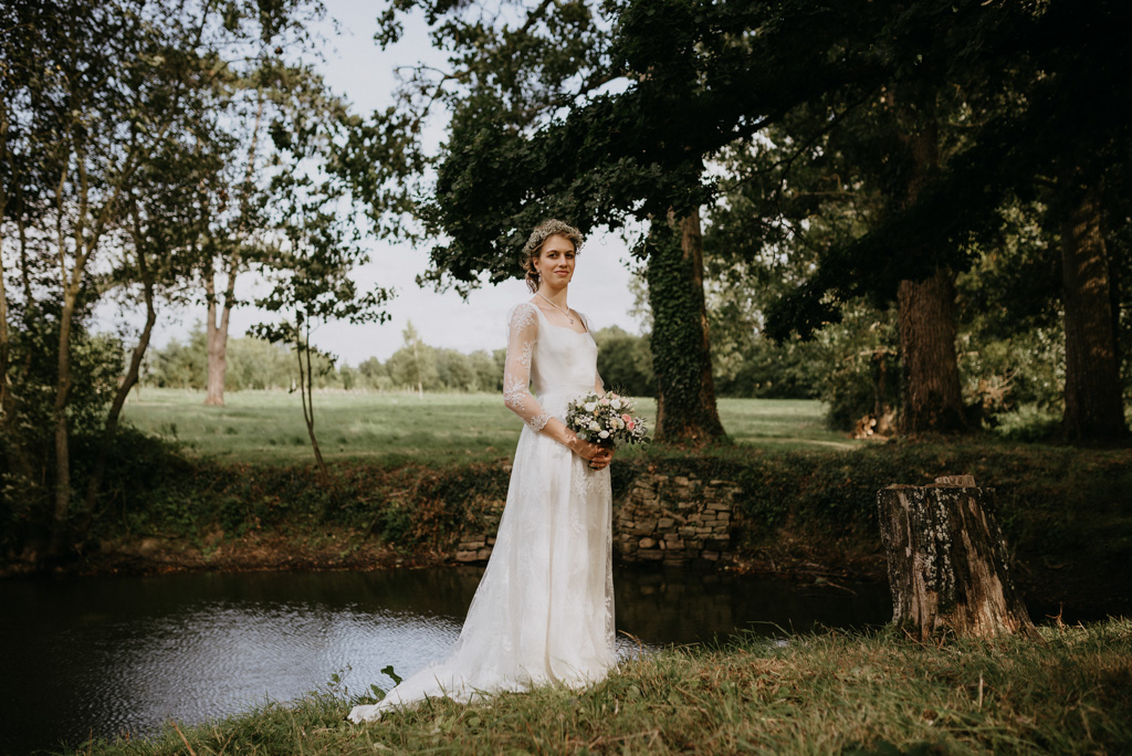mariée pose étang bouquet arbre