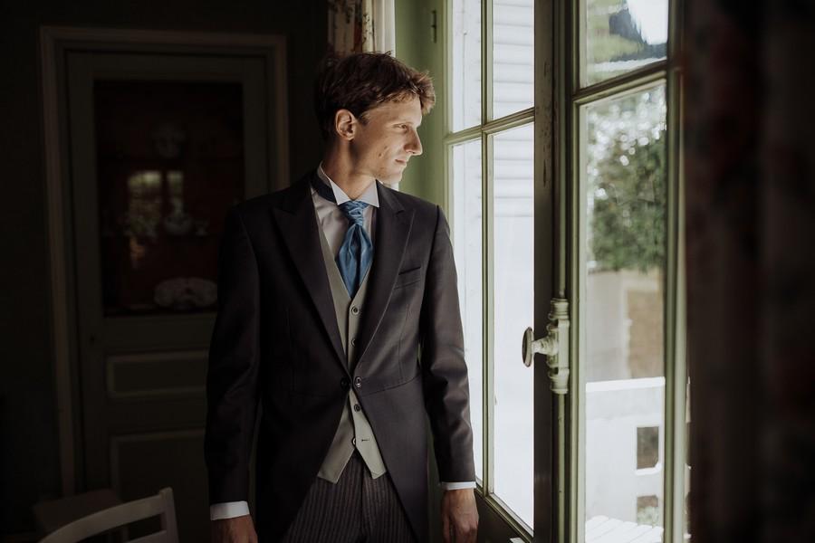marié prêt regard dehors porte lumière douce
