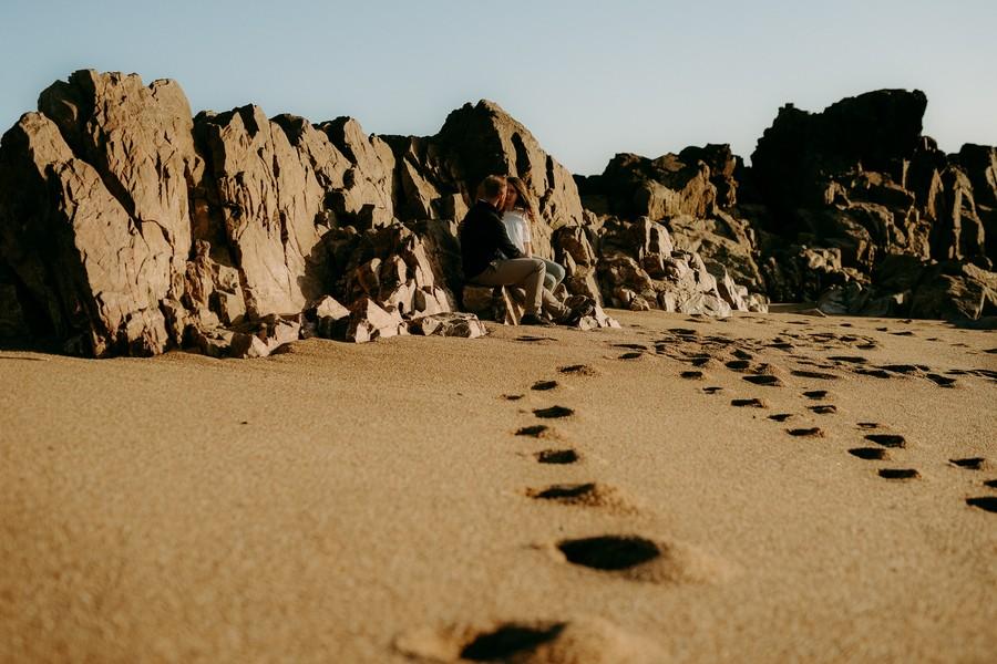 rochers couple assis empreintes sable ciel bleu
