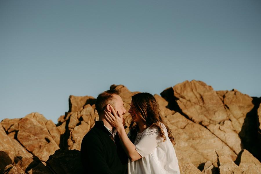 couple engagement se regarde ciel bleu rochers sourire