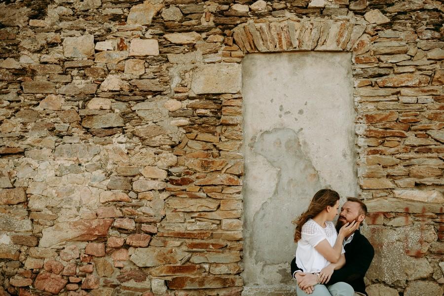 couple assis maison pierre porte caresse visage