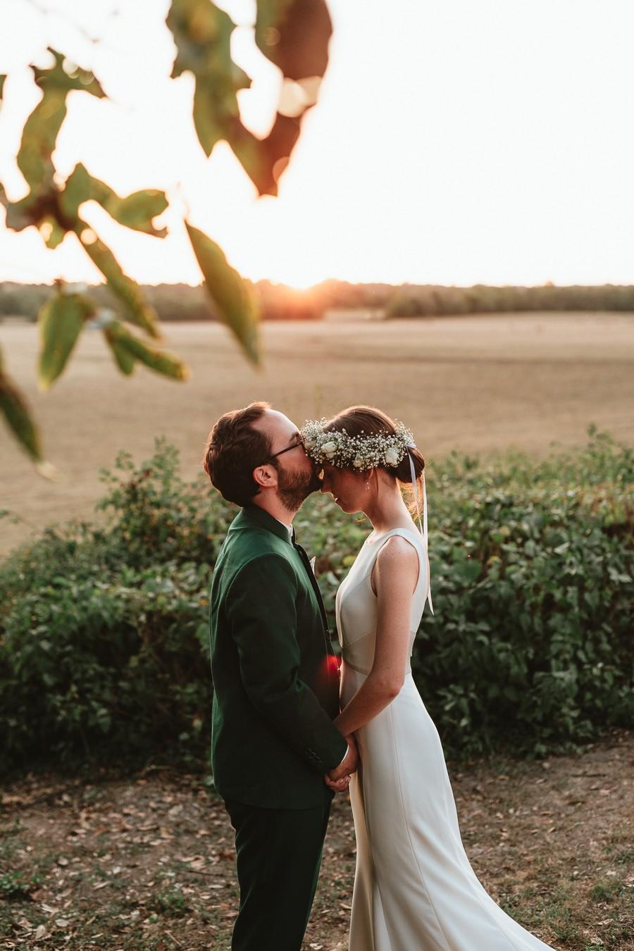 couple mariés contre-jour marié embrasse mariée