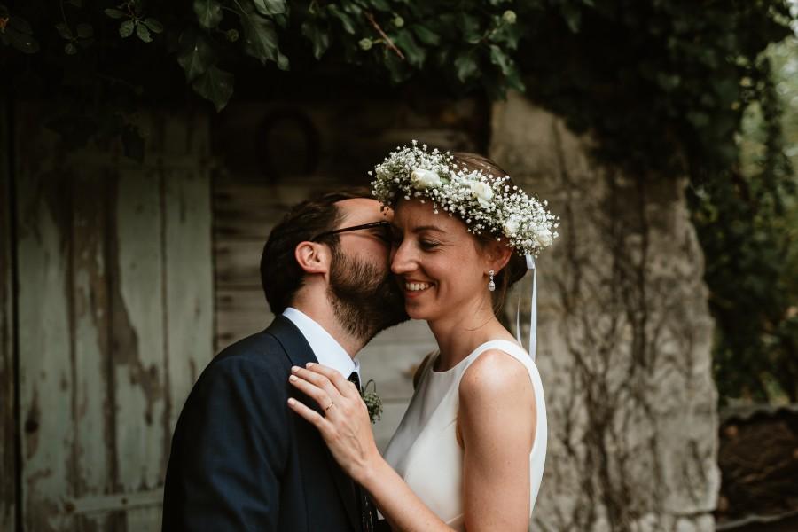 couple mariés s'embrasse porte bois lierre lumière douce